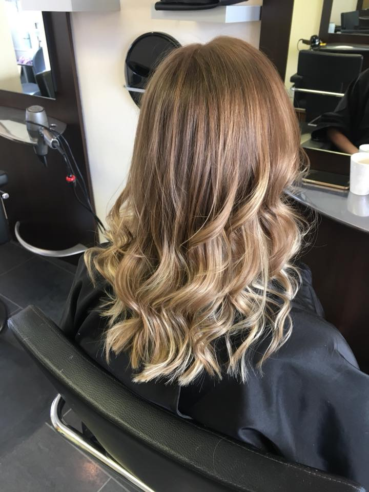 Woman after having a color, cut and style. Long, curled brown hair with blonde balayage
