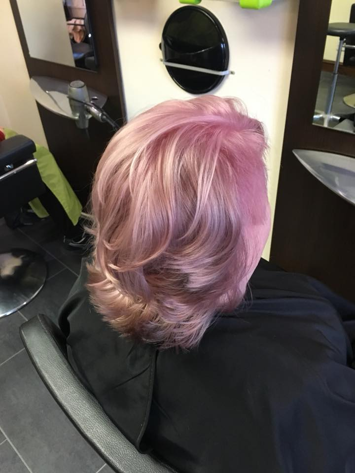 Image of women after having a colour and cut with her new pink hair colour.