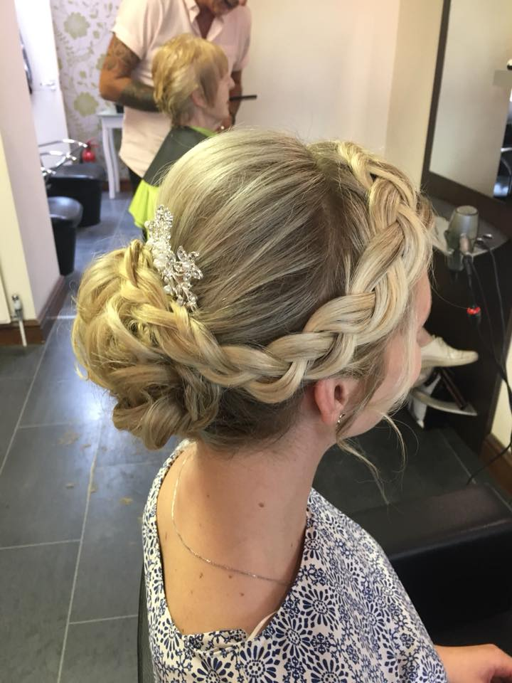 Woman with blonde and brown hair with a freshly done hair up with an accessory in her hair to finish it off.