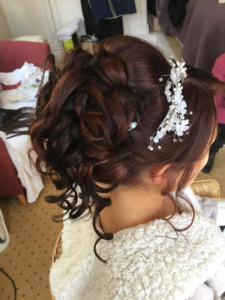 Bride after having her slightly red hair put into a pretty hair up for her wedding,
